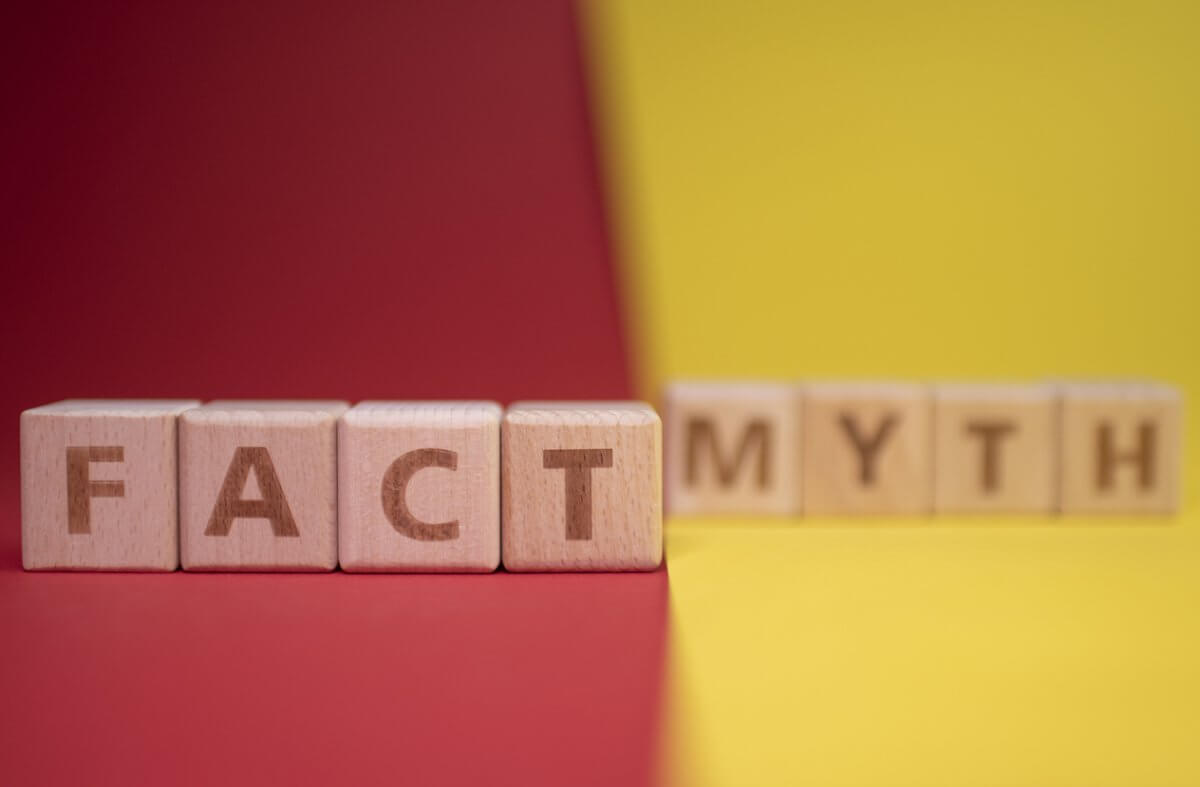 "Photograph of wooden blocks with words on them that say ""fact"" and ""myth"" in front of a red and yellow background."