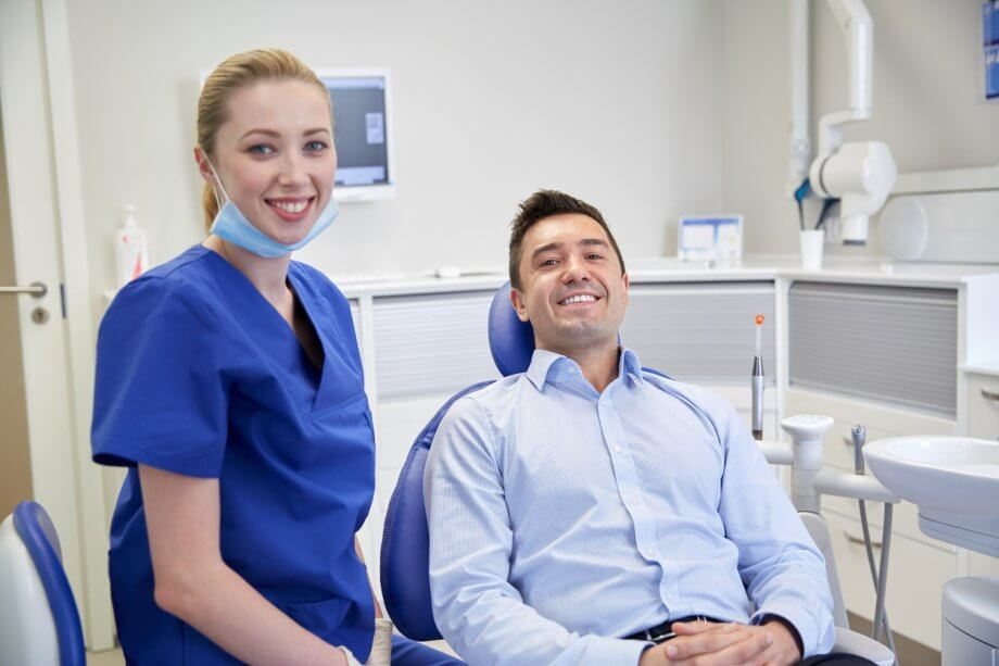 Professional man in a button-up shirt sitting in a dentists chair smiling next to a female dental hygienist dressed in blue