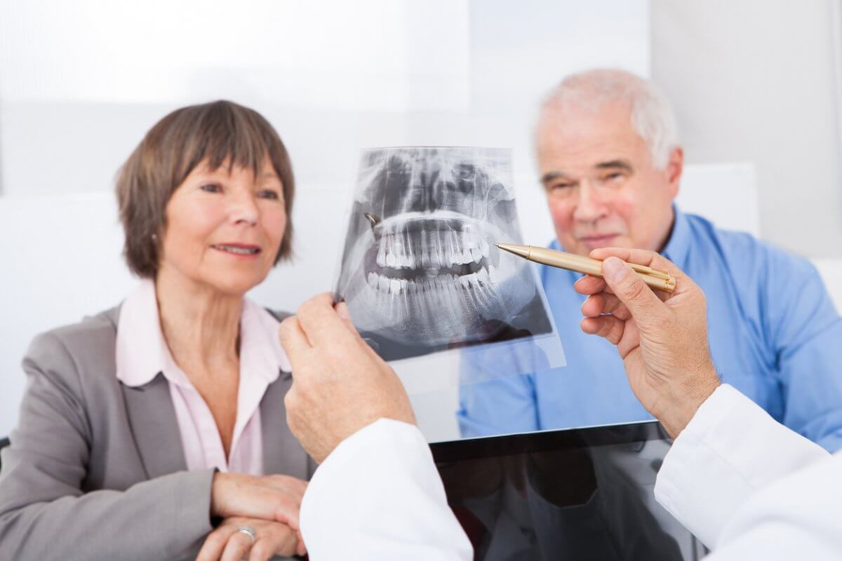 A dentist is holding up an x-ray and pointing to it, talking to an older male and female.