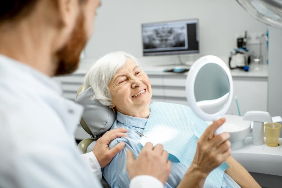 Older woman sitting in a dentists chair looking at herself in a handheld mirror & smiling as the dentist sits beside her.