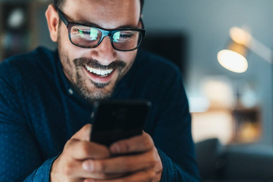 smiling man texting on cell phone