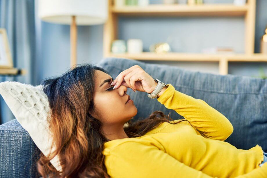 woman laying on couch with headache