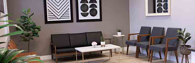 waiting room with black chairs and geometric artwork