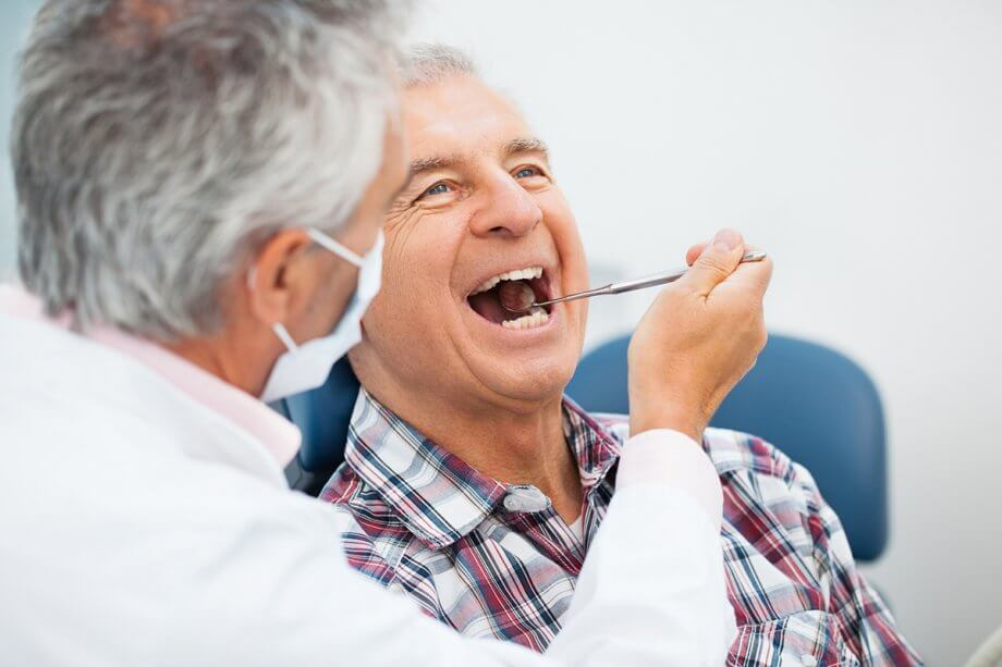 dentist using dental mirror to look in patient's mouth