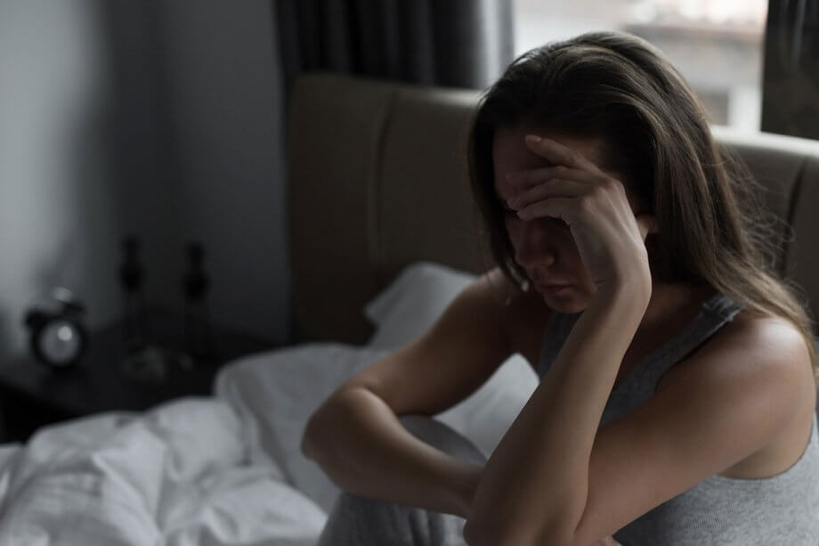 woman sitting up in bed holding head